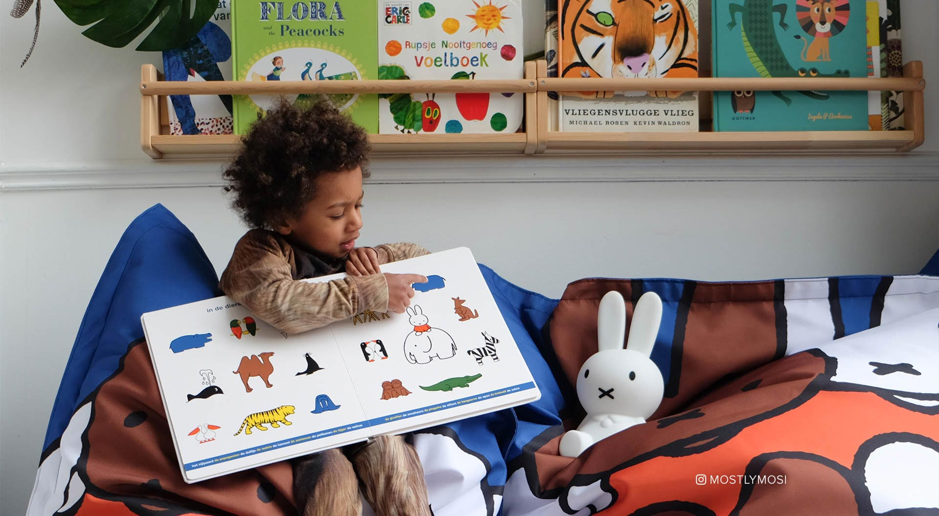 Miffy Dreambags, Mosi reading Dick Bruna illustrated book with Miffy First Light photo by Rio van der Oes